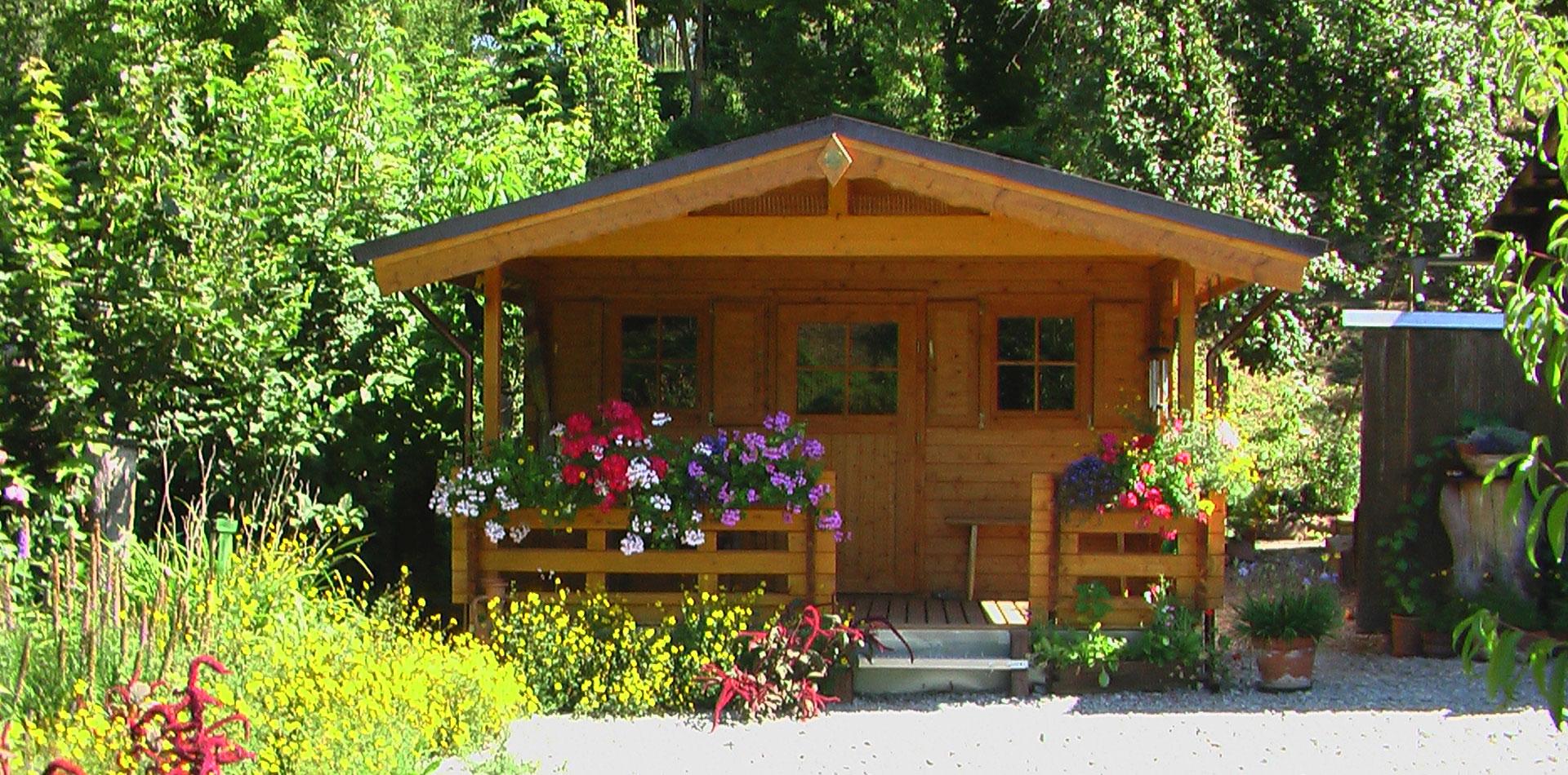 WEKA Gartenhaus mit Terrassengeländer an einem schönen Sonnentag