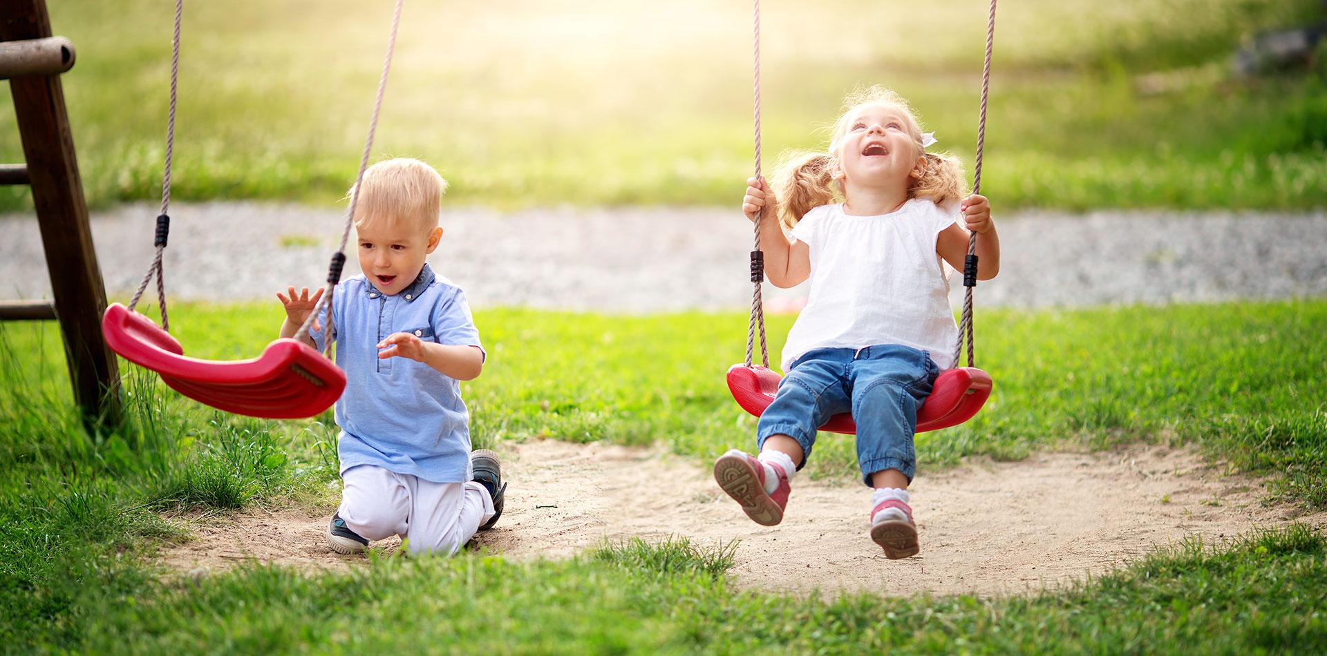 Die Kinderschaukel entdecken der Junge und das Mädchen im Garten